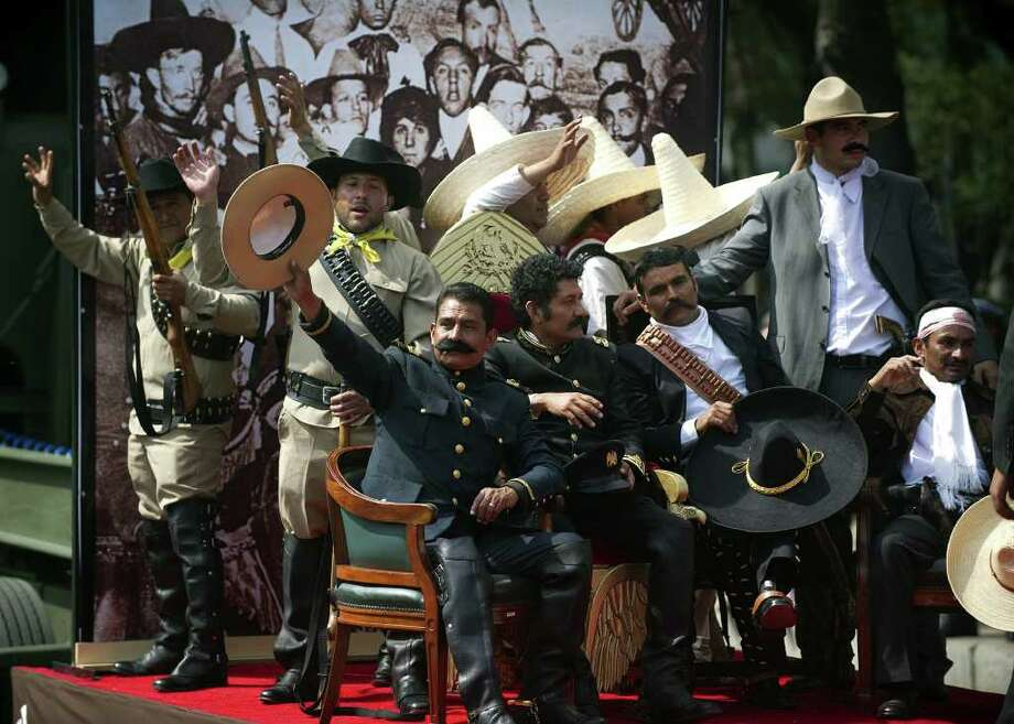 Men representing Mexican revolutionary leaders Francisco Villa (L) and Emiliano Zapata (R) perform during a military parade commemorating the 101th anniversary of the Mexican Revolution along Reforma Avenue on November 20, 2011 in Mexico City.  AFP PHOTO/Yuri CORTEZ Photo: YURI CORTEZ, Getty Images / 2011 AFP