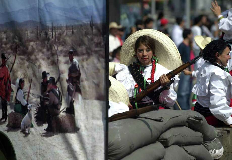 "A woman dressed as an ""Adelita"" -woman warrior of the Mexican Revolution- performs during a military parade commemorating the 101th anniversary of the Mexican Revolution along Reforma Avenue on November 20, 2011 in Mexico City.  AFP PHOTO/Yuri CORTEZ Photo: YURI CORTEZ, Getty Images / 2011 AFP"