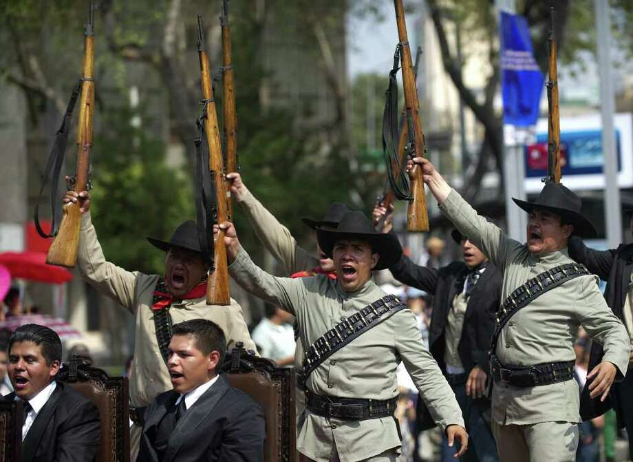 Men representing revolutionaries perform during a military parade commemorating the 101th anniversary of the Mexican Revolution along Reforma Avenue on November 20, 2011 in Mexico City.  AFP PHOTO/Yuri CORTEZ Photo: YURI CORTEZ, Getty Images / 2011 AFP