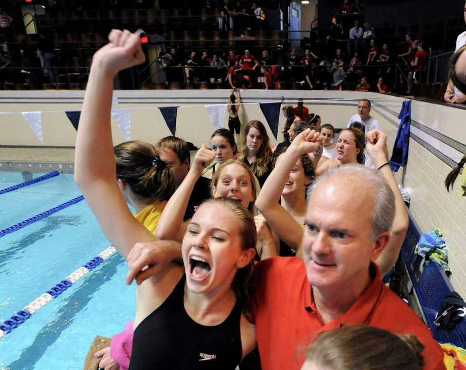 Greenwich High School swimmer Lauren Church, left, pumps her fist in the air while celebrating with Greenwich High School swim coach Dick Hawks, right, after Greenwich High School won the girls CIAC State Open Swimming Championships at Yale University, New Haven, Saturday, Nov. 19, 2011. Photo: Bob Luckey / Greenwich Time