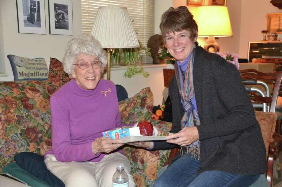 Meals-On-Wheels board member Pam Crigler makes a personal delivery to  very appreciative and cheerful Karola Schuette. Photo: Jeanna Petersen Shepard