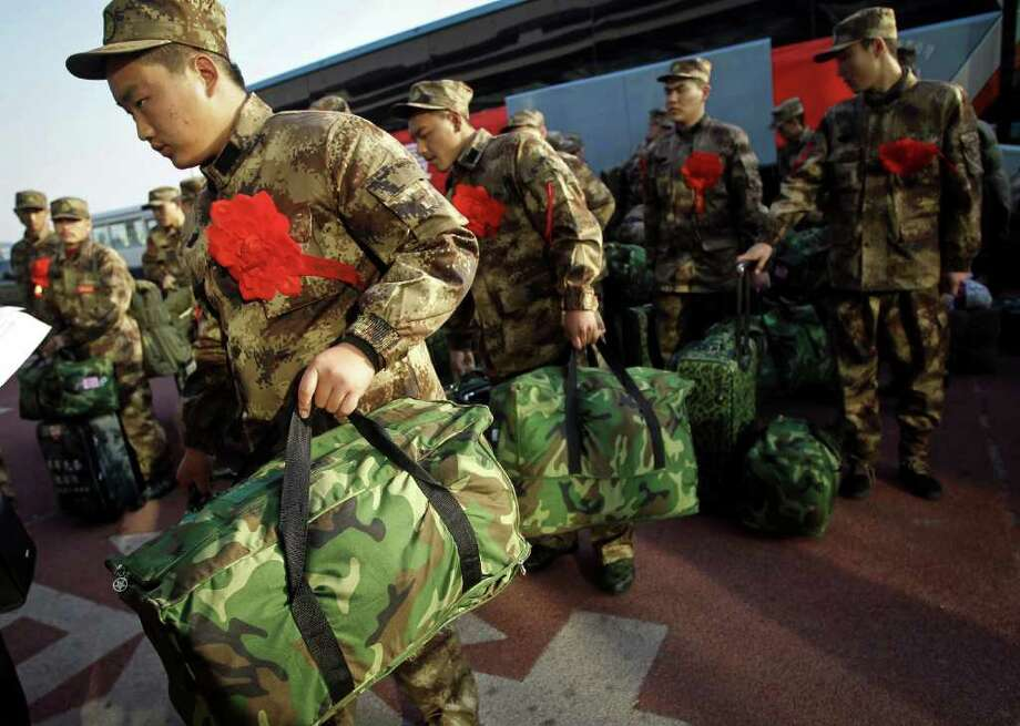 In this photo taken Sunday, Nov. 20, 2011, newly-recruited military soldiers prepare to board a plane after attending a departure ceremony in Beijing, China. The 280 recuruits, more than 60 percent were university soldiers, enlisted for posts in Tibet to start their military service. (AP Photo) CHINA OUT / CHINATOPIX