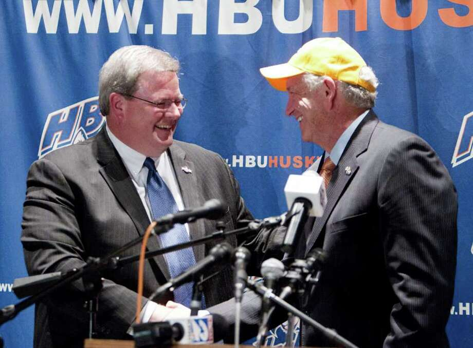 Southland Conference Commissioner Tom Burnett, left , shakes hands with HBU President Robert B. Sloan Jr. after it was announced during a press conference that Houston Baptist University has accepted an invitation to join the Southland Conference beginning with 2013-14 academic year. The announcement was made on campus November 21, 2011 in Houston. The Huskies will also add football  to their current lineup of sports and begin Southland Conference play on 2014. Photo: Bob Levey, Houston Chronicle / ©2011 Bob Levey