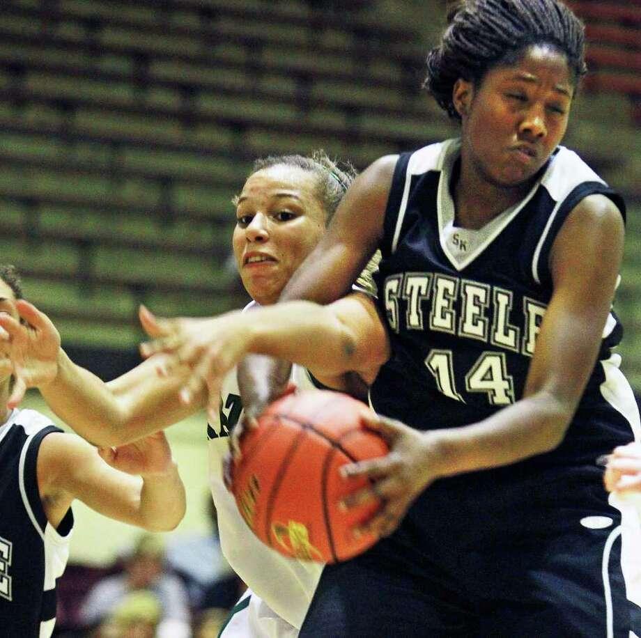 Reagan's Corrigan Tibbs (left) battles for a rebound with Steele's McKenzie Calvert during last week's game. Photo: TOM REEL, SAN ANTONIO EXPRESS-NEWS / © 2011 San Antonio Express-News