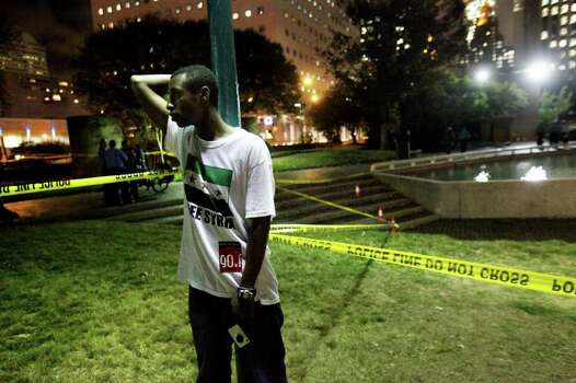 Jamin Stocker looks at fellow occupiers interviewed by Houston Police after a gunman walks into Occupy Houston Camp at Tranquility Park and shoots into air on Monday, Nov. 21, 2011, in Houston. Photo: Mayra Beltran, Houston Chronicle / © 2011 Houston Chronicle