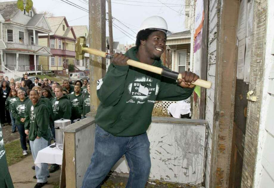 Sterling Major, 19, wields a sledgehammer on a home in Schenectady where he will be getting hands-on training in construction work that emphasizes energy efficiency through the YouthBuild program.