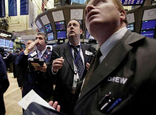 Traders work on the floor of the New York Stock Exchange Monday, Nov. 21, 2011. Stocks are taking a sharp fall in early trading Monday amid reports that a congressional committee will fail to agree on a plan to cut the U.S. government's budget deficit.(AP Photo/Richard Drew) Photo: Richard Drew