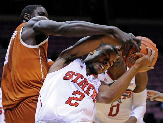 Texas forward Alexis Wangmene, left, defends North Carolina State guard Lorenzo Brown during the first half of an NCAA college basketball game in the Legends Classic on Monday, Nov. 21, 2011, in East Rutherford, N.J. Photo: AP