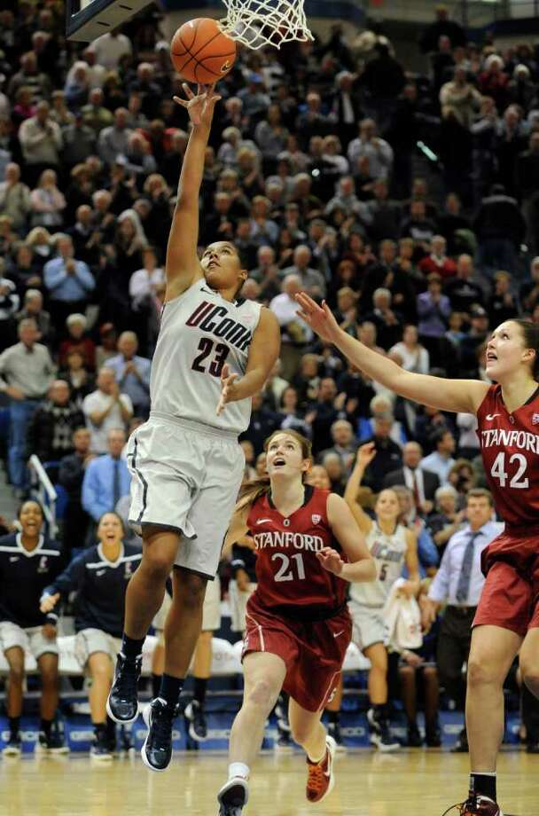 Connecticut's Kaleena Mosqueda-Lewis (23) goes up for a basket while guarded by Stanford's Sara James (21) and Sarah Boothe (42) in the second half of an NCAA college basketball game Hartford, Conn., Monday, Nov. 21, 2011.   Mosqueda-Lewis was top scorer for Connecticut with 25 points. (AP Photo/Jessica Hill) Photo: Jessica Hill, AP / AP2011