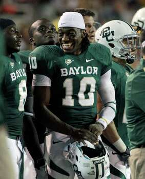 Baylor quarterback Robert Griffin III (10) smiles as he talks with teammates on the sideline late in the third quarter of an NCAA college football game against Stephen F. Austin, Saturday, Sept. 17, 2011, in Waco, Texas. Baylor celebrated their highest ranking since October 1991 by routing Stephen F. Austin 48-0 S in a game that was ended in the third quarter because of lightning. Photo: AP