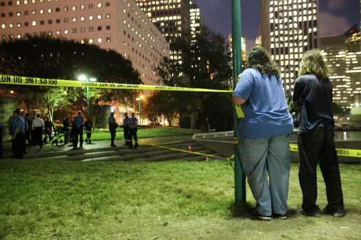 MAYRA BELTRÁN : CHRONICLE  SHOOTING SCENE: Occupy Houston demonstrators watch as their friends are interviewed after Monday night's shooting. Photo: Mayra Beltran / © 2011 Houston Chronicle