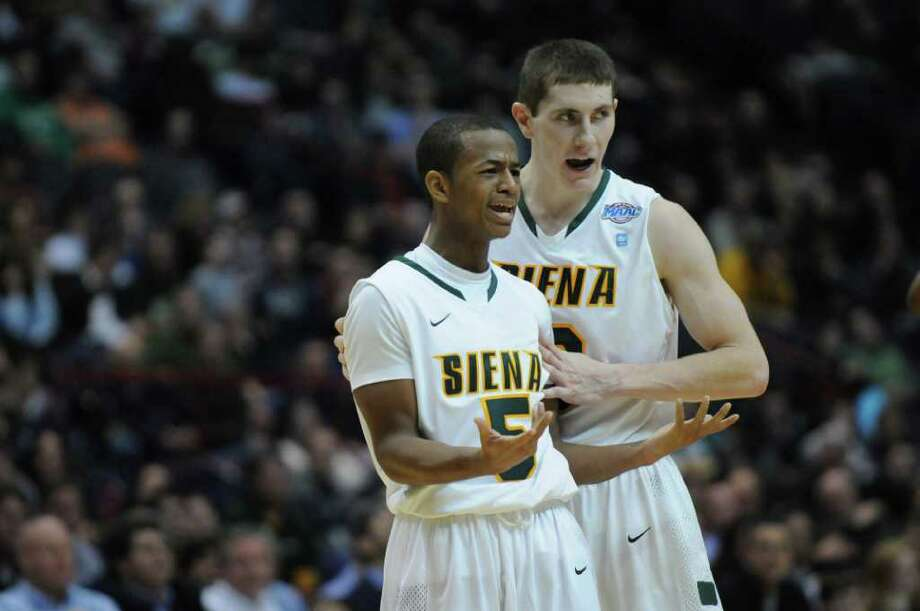 Siena's Kyle Downey, right, tries to calm teammate Evan Hymes, left, after Hymes was called as part of double technical foul during the second half of Siena's 64-58 loss to St. Bonaventure at the Times Union Center on Monday night Nov. 21, 2011 in Albany, NY. (Philip Kamrass / Times Union ) Photo: Philip Kamrass / 00015373B