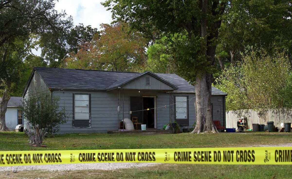 Crime-scene tape surrounds the scene after a man and his teenage daughter were shot to death by masked men in a home invasion in Texas City on Monday. (Cody Duty/Chronicle)