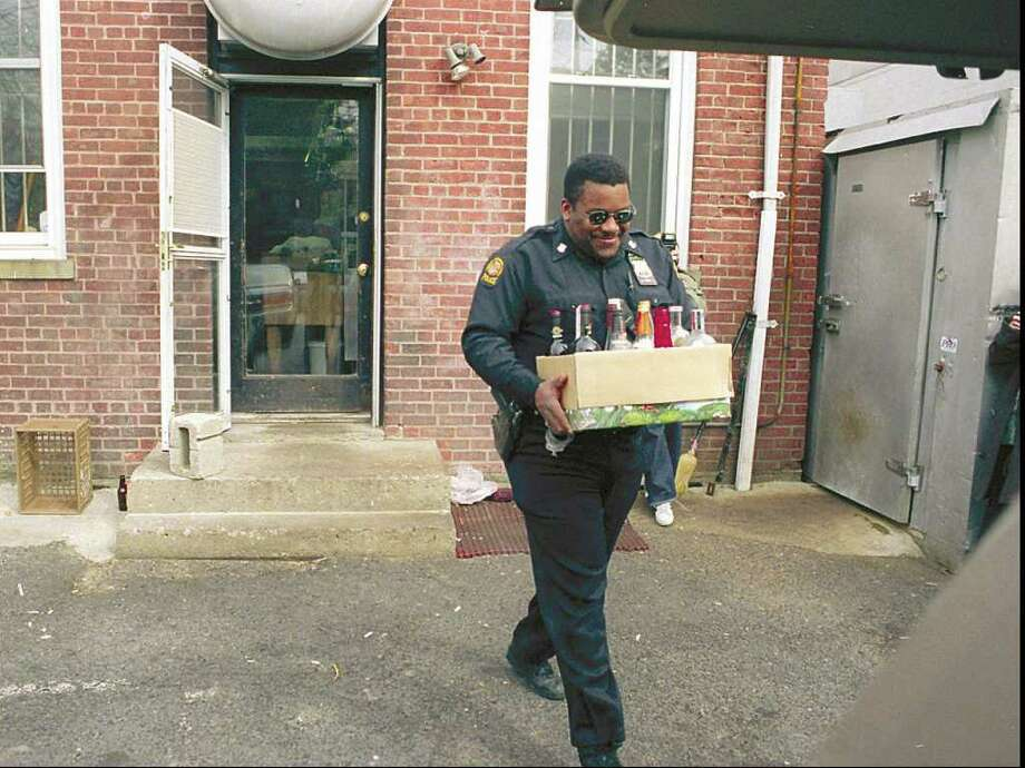 Greenwich Police Officer Terral Hardy, shown here in 1999 removing bottles of alcohol from a Greenwich restaurant that was found to be illegally selling liquor without a license, retired from the department Nov. 1. Photo: Greenwich Time File