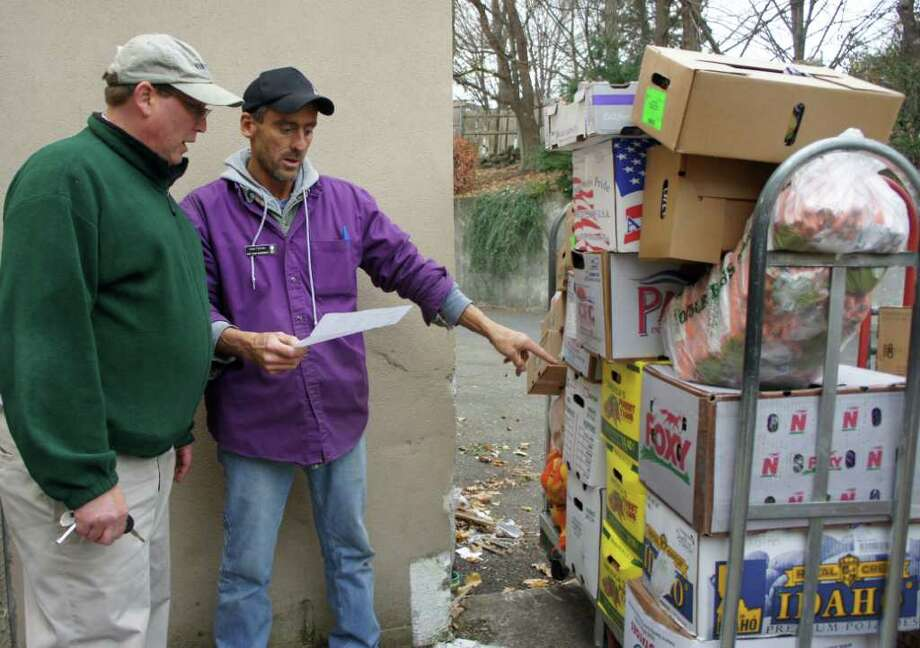 Stop & Shop produce manager Sam Farina, right, and Saugatuck Congregational Church mission board chairman Randy Christophersen inspect on Tuesday, Nov. 22, 2011, produce donated by Stop & Shop to the church for its Thanksgiving feast. Photo: Paul Schott / Westport News