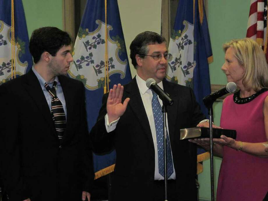 Rob Mallozzi being sworn in as First Selectman alongside his son Robby IV and wife Liz. Photo: Paresh Jha