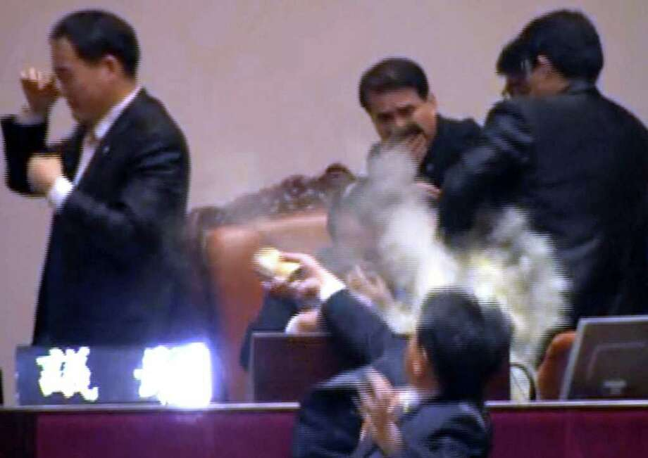 Rep. Kim Seon-dong, bottom, of the opposition Democratic Labor Party, explodes tear gas in front of the speaker's chair to block National Assembly Vice Speaker Chung Eui-hwa, center, from pushing for the procedure to handle a pending bill on ratification of a South Korea-U.S. free trade agreement at the National Assembly in Seoul, South Korea, Tuesday, Nov. 22, 2011. South Korea's parliament ratified a long-stalled free trade deal with the United States on Tuesday after ruling party lawmakers forced a vote amid shouts and shoves from opposition rivals. (AP Photo/Yonhap) KOREA OUT / Yonhap