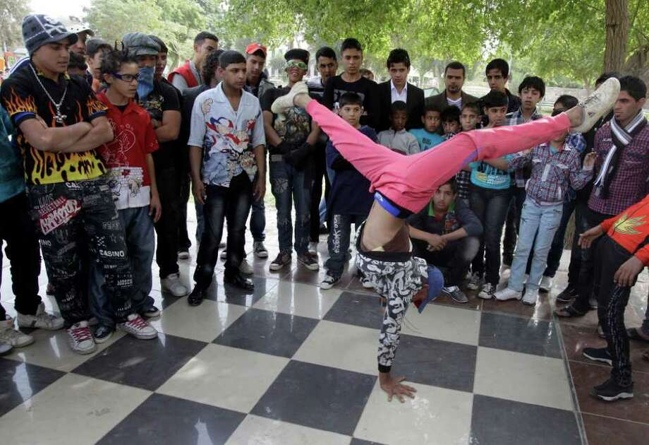 KARIM KADIM : ASSOCIATED PRESS  STAND BACK: An Iraqi boy dances to hip-hop music in Baghdad, Iraq. To many young Iraqis, imitating the U.S. troops they watched for years is their way of pursuing the American dream.  Other Iraqis view their behavior as strange or offensive. Photo: Karim Kadim / AP