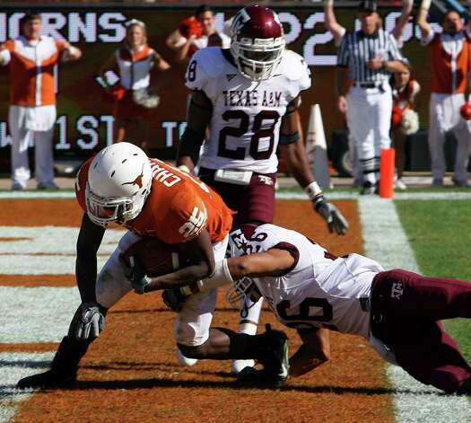 FOR SPORTS - Longhorns' Jamaal Charles scores a touchdown as he is defended by Aggies' Devin Gregg and  Aggies' Japhus Brown looks on Friday Nov. 24, 2006 at Texas Memorial Stadium in Austin, Texas. The Aggies went on to win 12-7. PHOTO BY EDWARD A. ORNELAS/STAFF Photo: EDWARD A. ORNELAS, SAN ANTONIO EXPRESS-NEWS / SAN ANTONIO EXPRESS-NEWS