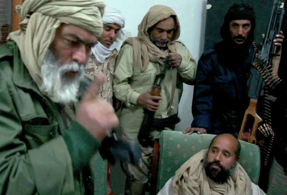 ASSOCIATED PRESS SURROUNDED:  In this image taken from video made available Tuesday, Moammar Gadhafi's son Seif al-Islam is surrounded by soldiers shortly after his capture on Saturday. / APTN