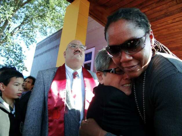 Ann Wolfe (right) consoles Virginia Souza, widow of boxing cutman Joe Souza, as son Arthur Souza looks on. Photo: BILLY CALZADA, SAN ANTONIO EXPRESS-NEWS / gcalzada@express-news.net