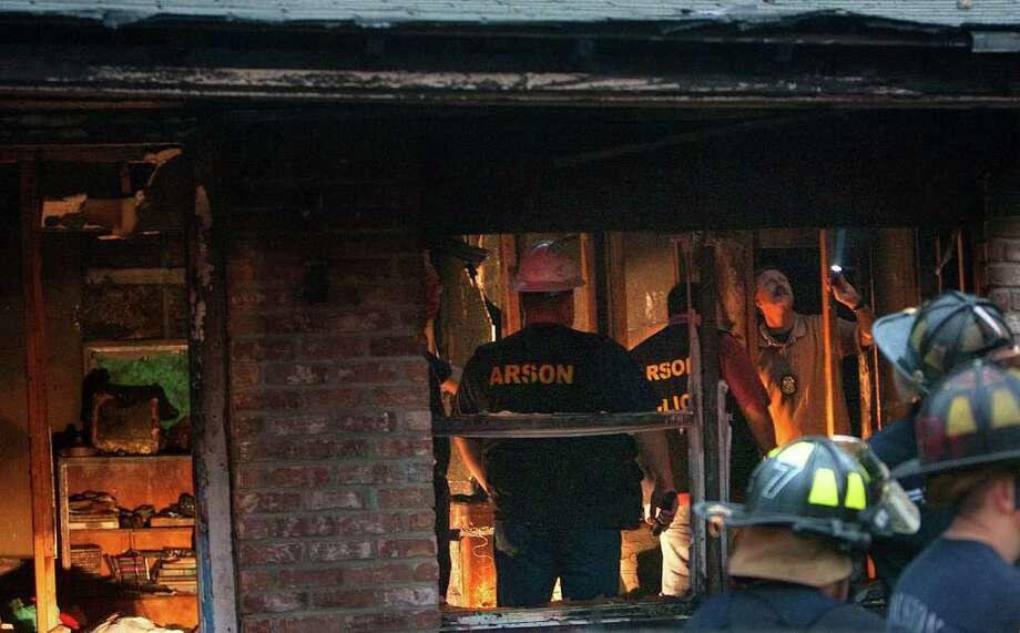 Firefighters investigate the cause of a fatal fire in the 5800 block of Crane Street Tuesday, Nov. 22, 2011, in Houston. Photo: Cody Duty, Houston Chronicle / © 2011 Houston Chronicle