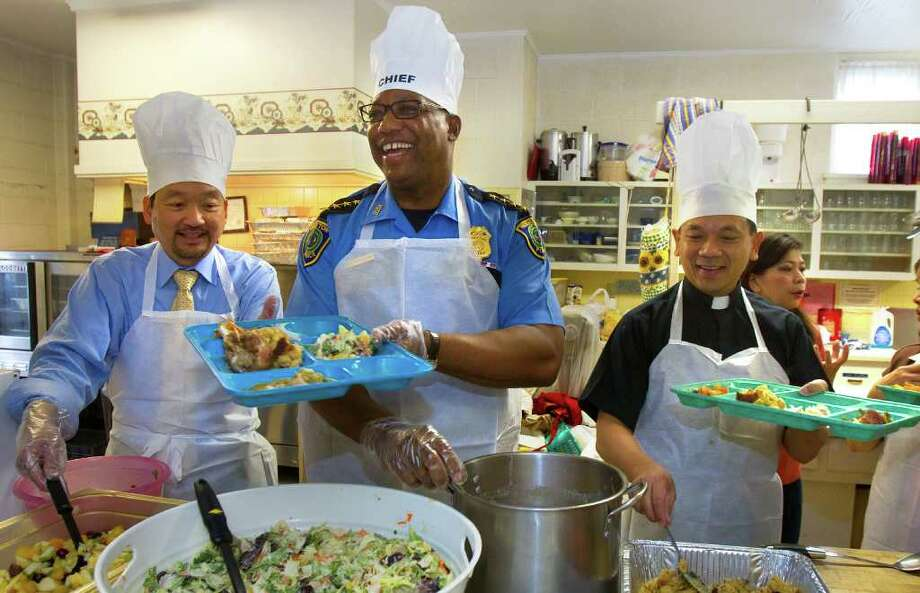Houston Police Chief Charles A. McClelland, Jr., center, smiles as he prepares a Thanksgiving meal with Deputy Director Larry Yium, left, and Father Tam Pham, right, at St. Paul Episcopal Church, Tuesday, Nov. 22, 2011, in Houston. Photo: Cody Duty, Houston Chronicle / © 2011 Houston Chronicle