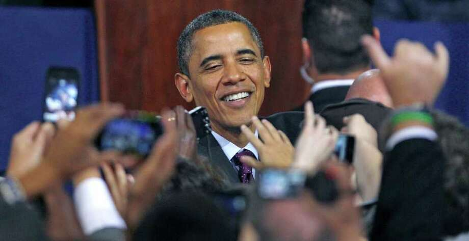 President Barack Obama shakes hands after an address where he remarked on the American Jobs Act, Tuesday, Nov. 22, 2011, at Central High School in Manchester, N.H. (AP Photo/Charles Krupa) Photo: Charles Krupa / AP