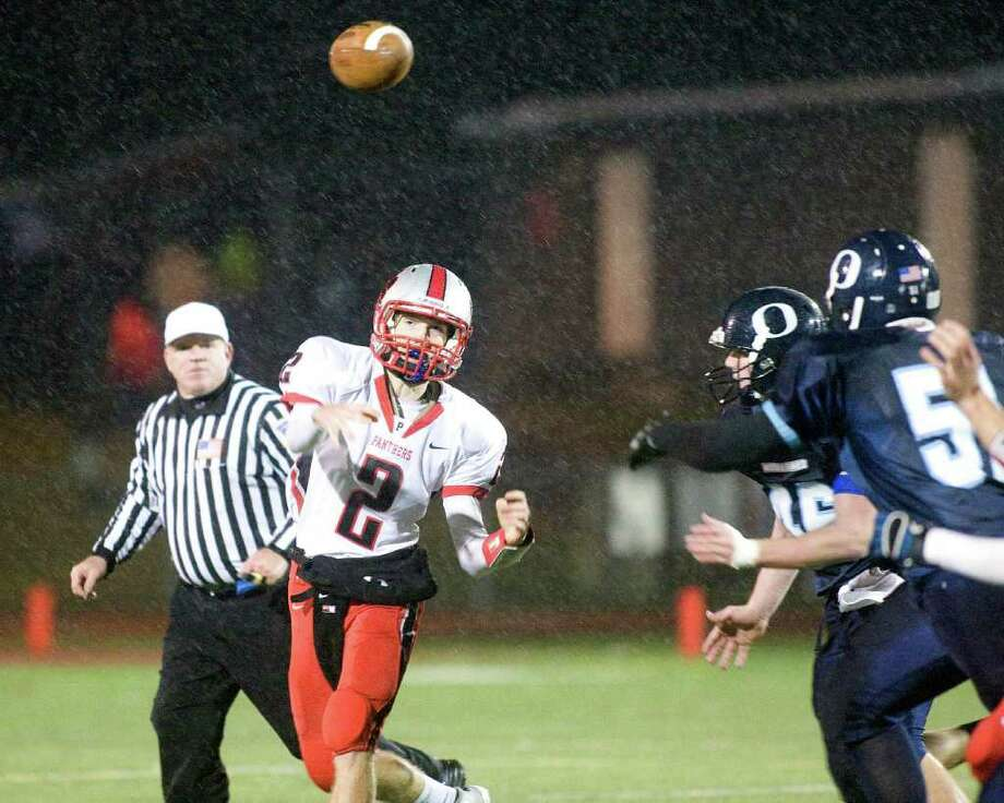 Pomperaug quarterback Eric Beatty completes a pass in the rain against Oxford during an SWC football game Tuesday night, Nov. 22, 2011, at Pomperaug High School in Southbury. Photo: Barry Horn / The News-Times Freelance