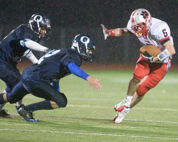 Pomperaug's Matt Paola uses a stiff arm to try to get around Oxford's Brennen Diaz during their SWC football game Tuesday night, Nov. 22, 2011, at Pomperaug High School in Southbury. Photo: Barry Horn / The News-Times Freelance