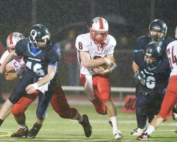 Pomperaug's Andrew Reel (8) finds running room between Oxford's Brian Spicer, left, and David Carbonaro during their SWC football Tuesday night, Nov. 22, 2011, at Pomperaug High School in Southbury. Photo: Barry Horn / The News-Times Freelance
