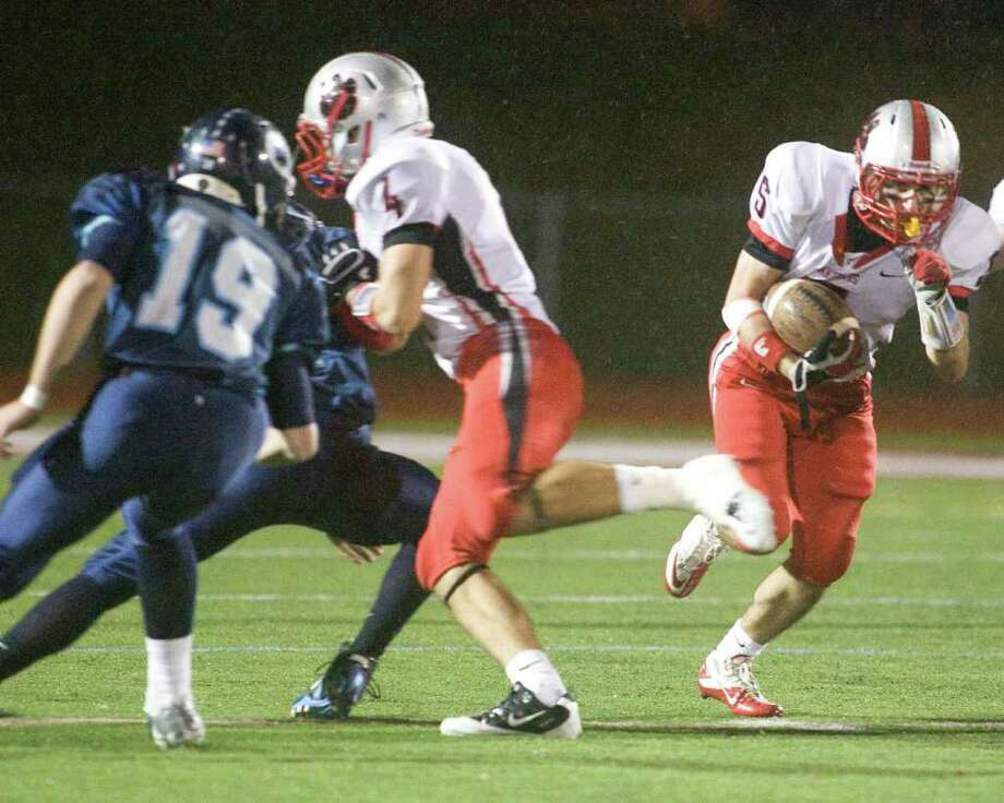 Pomperaug's Matt Paola uses a block from Tyler Valenti (4) to pickup yardage during the Panthers' SWC football game against Oxford Tuesday night, Nov. 22, 2011, at Pomperaug High School in Southbury. Photo: Barry Horn / The News-Times Freelance