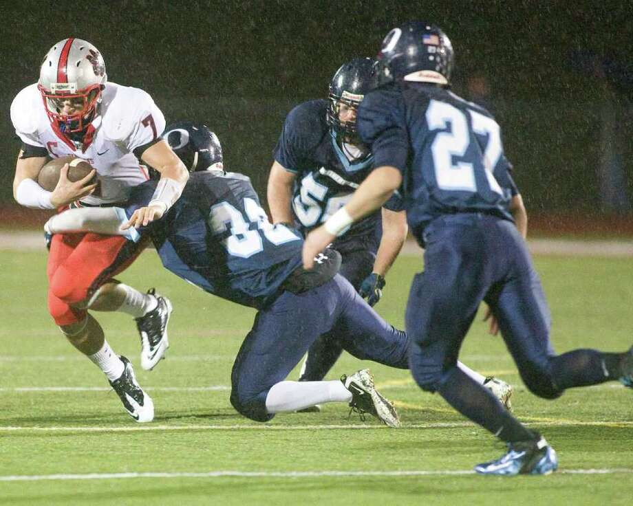 Oxford's Benjamin Blue (32) brings down Pomperaug's Garrett DeLotto during their SWC football game Tuesday night, Nov. 22, 2011, at Pomperaug High School in Southbury. Photo: Barry Horn / The News-Times Freelance