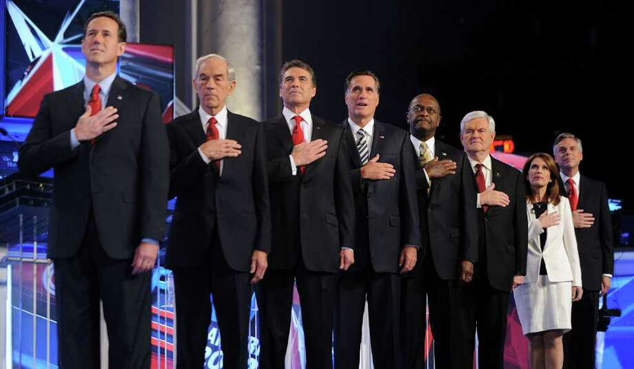 OLIVIER DOULIERY : ABACA PRESS/MCT MAKING THE PLEDGE: Rick Santorum, from left, Ron Paul,  Rick Perry, Mitt Romney, Herman Cain, Newt Gingrich, Michele Bachmann and Jon Huntsman gather on stage prior to the start of the Republican presidential debate Tuesday at DAR Constitution Hall in Washington. Photo: Olivier Douliery / Abaca Press