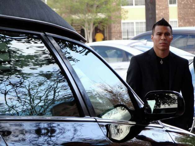 Boxer Raul Martinez watches as a hearse carrying the casket of legendary boxing cutman Joseph Souza arrives for his funeral Mass at  Resurrection of the Lord Catholic Church on Tuesday, Nov. 22, 2011. Photo: BILLY CALZADA, SAN ANTONIO EXPRESS-NEWS  / gcalzada@express-news.net
