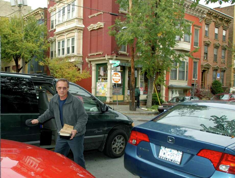 """Gary Finning, a """"Meals on Wheels"""" driver, emerges from his van to deliver food to a client on Grand Street in Albany on Nov. 8, 2007. (Luanne M. Ferris / Times Union archive) Photo: LMF, ALBANY TIMES UNION / ALBANYTIMES UNION"""