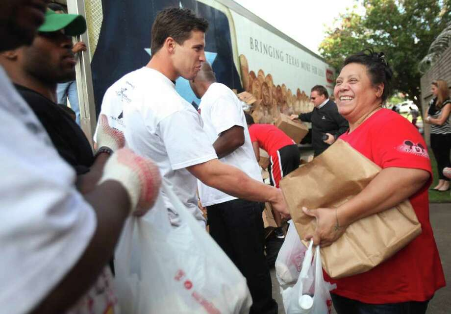 Houston Texans Brian Cushing shakes hands with Mary Lou Olveda, 48, as the players hand out Thanksgiving meals to families from Houston's Fifth Ward community at the Fifth Ward Church of Christ on Tuesday, Nov. 22, 2011, in Houston. Photo: Mayra Beltran, Houston Chronicle / © 2011 Houston Chronicle
