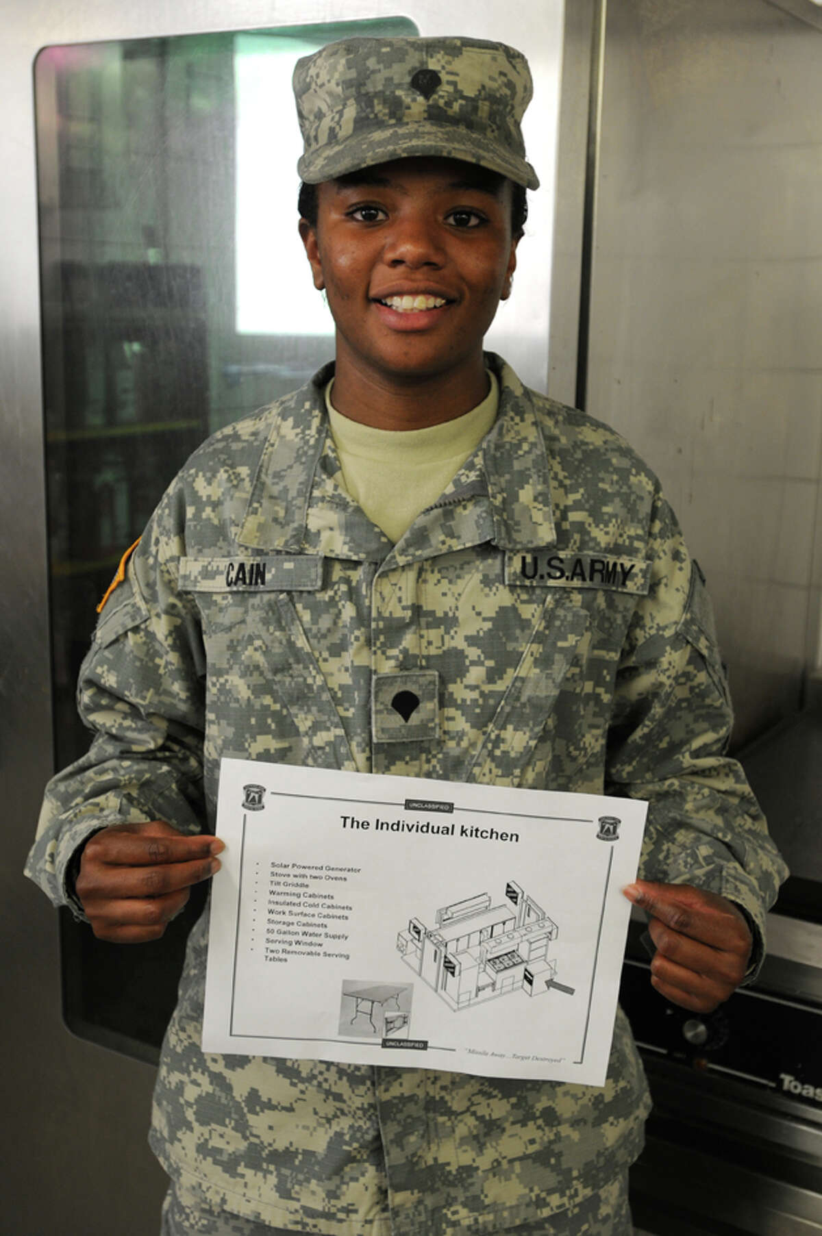 Spc. Shaunta Cain of U.S. Army Europe s Bravo Battery, 5th Battalion, 7th Air Defense Artillery displays a sketch of her design for a compact Army field kitchen. The design earned Cain the first individual Army Food Advisor Innovation Award. (Photo by Spc. Joshua Leonard)