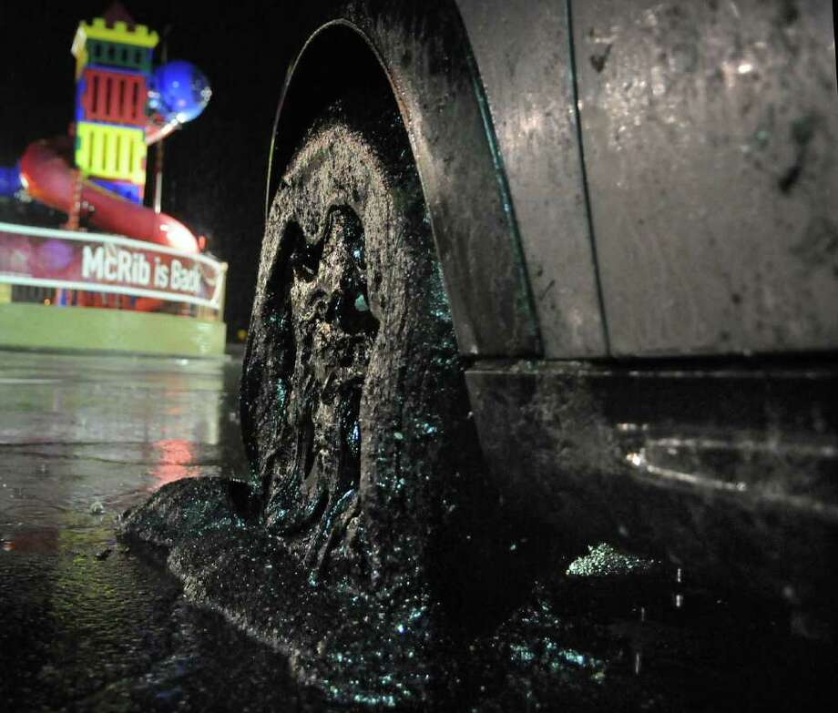 A car with its wheels covered in driveway sealant sits in a parking lot in Harmar, Pa., after exiting the Pennsylvania Turnpike Tuesday night, Nov. 22, 2011. A flood of the gooey material dropped from a tanker truck disabled more than 100 cars and damaged an unknown number of other vehicles along a nearly 40-mile stretch of the Turnpike, officials said. (AP Photo/Valley News Dispatch, Erica Hilliard)  PITTSBURGH POST-GAZETTE OUT; BUTLER EAGLE OUT Photo: Erica Hilliard / Valley News Dispatch