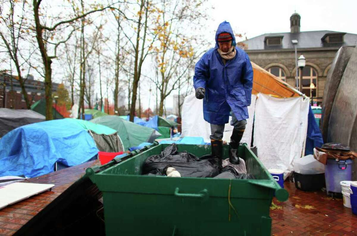 Carl Nakajima works to crush trash into a dumpster on Wednesday at the Occupy Seattle encampment at Seattle Central Community College. Members of the camp were working to clean trash and clean up their image as a board of community college trustees were voting to evict Occupy Seattle from Seattle Central Community College campus.