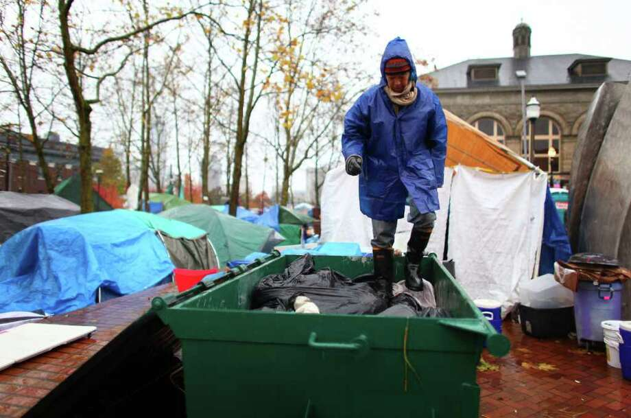 Carl Nakajima works to crush trash into a dumpster on Wednesday at the Occupy Seattle encampment at Seattle Central Community College. Members of the camp were working to clean trash and clean up their image as a board of community college trustees were voting to evict Occupy Seattle from Seattle Central Community College campus. Photo: JOSHUA TRUJILLO / SEATTLEPI.COM
