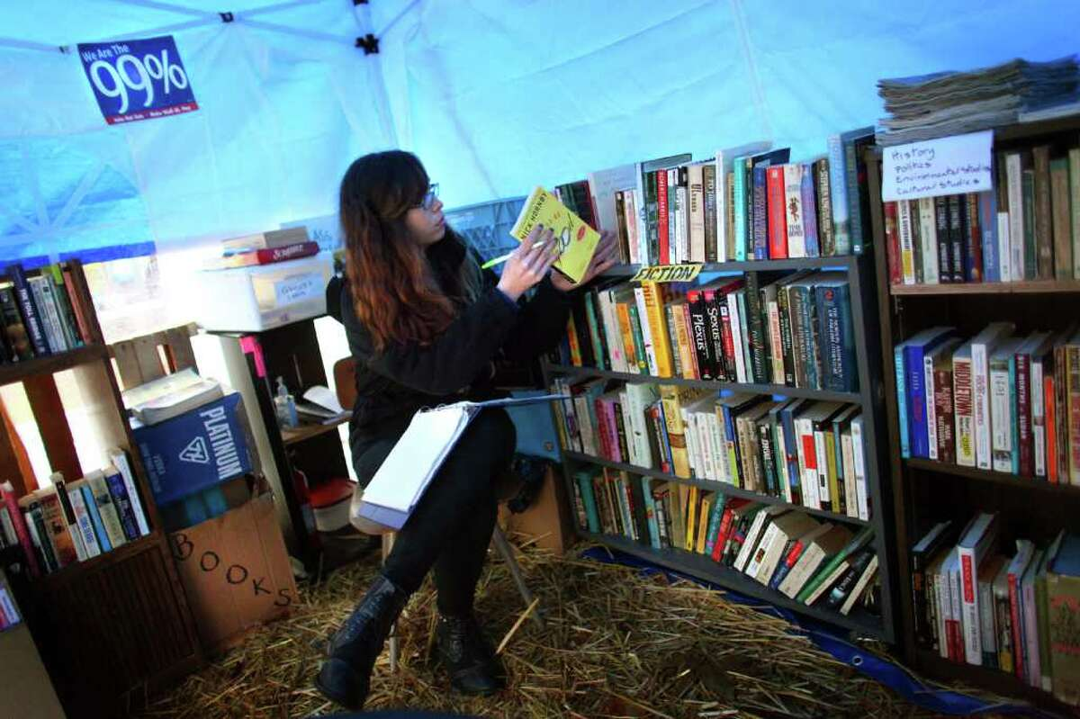 Amanda Jasso creates a log of books in the library tent on Wednesday, November 23, 2010 at the Occupy Seattle encampment at Seattle Central Community College. Members of the camp were working to clean trash from the camp as a board of community college trustees were voting to evict Occupy Seattle from Seattle Central Community College campus.