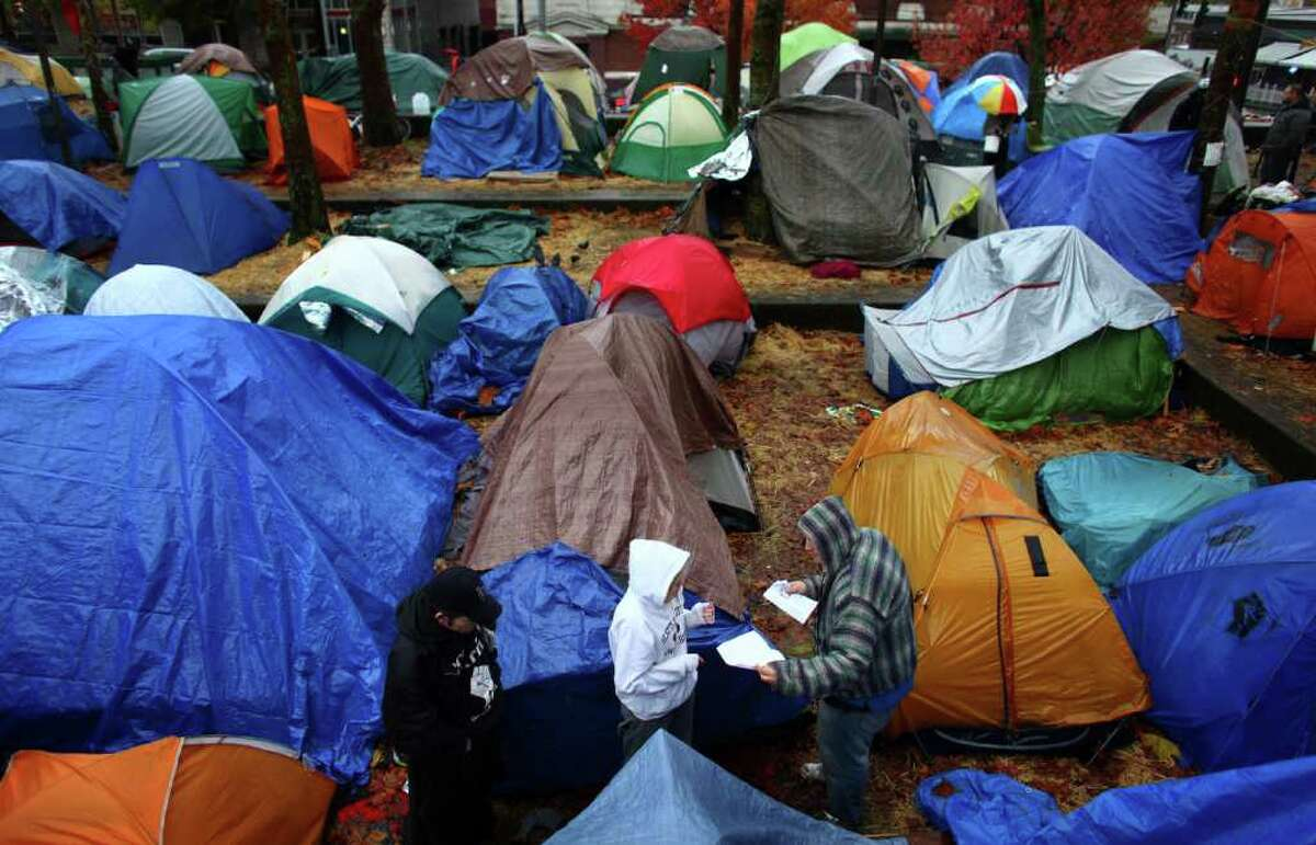 Camp rules are passed out to people living in tents on Wednesday, November 23, 2010 at the Occupy Seattle encampment at Seattle Central Community College. Members of the camp were working to clean trash from the camp as a board of community college trustees were voting to evict Occupy Seattle from Seattle Central Community College campus.