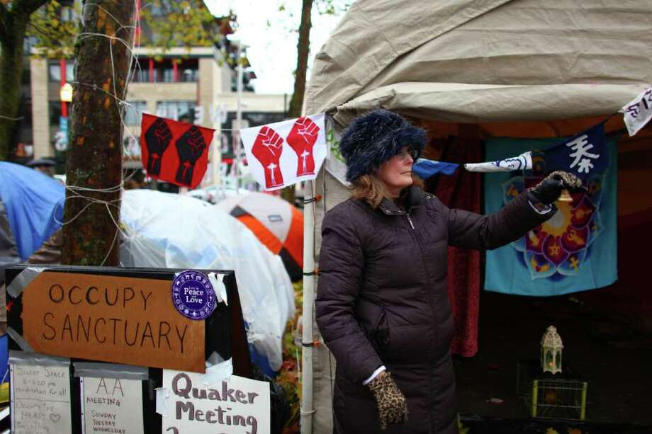 Rev. Karen Lindquist of Interfaith Community Church rings a bell outside the sanctuary tent at the Occupy Seattle encampment at Seattle Central Community College. Photo: JOSHUA TRUJILLO / SEATTLEPI.COM