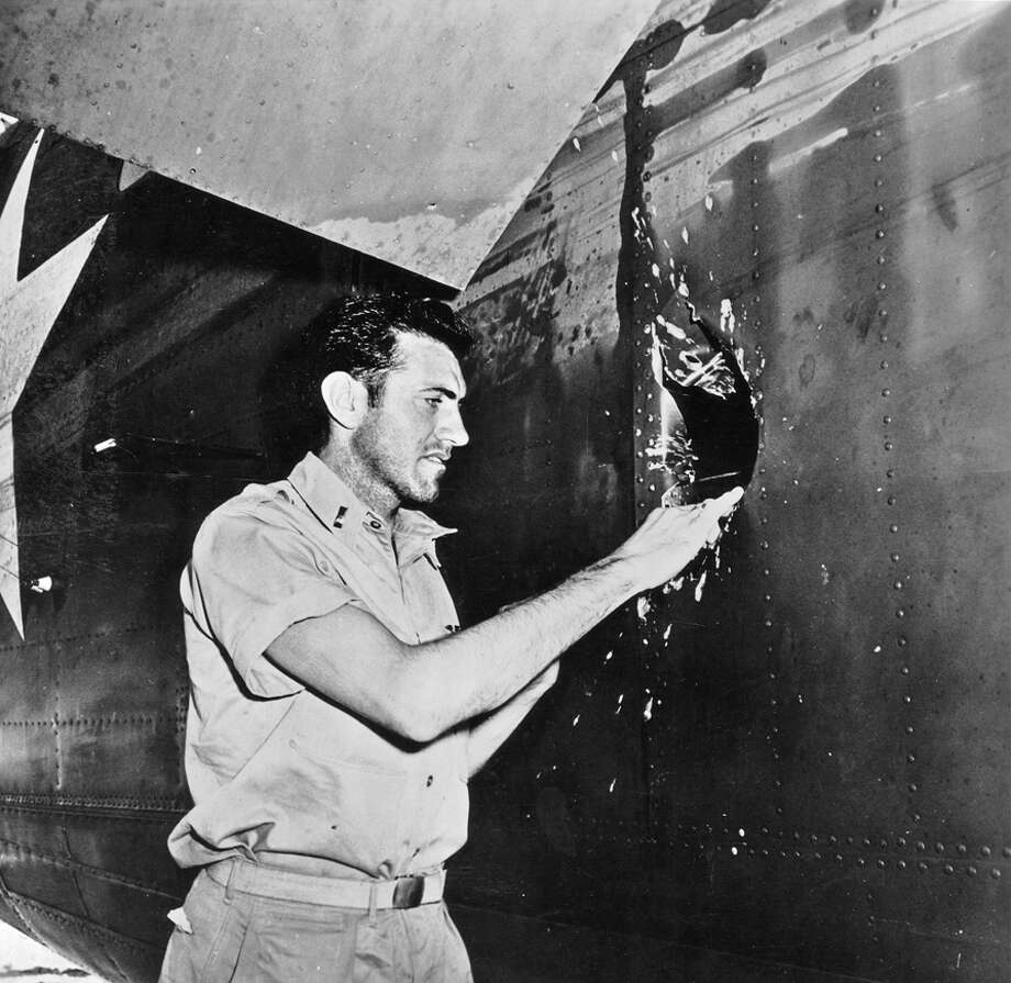 RANDOM HOUSE INSPECTION: Louis Zamperini examines a hole in Super Man, the B-24 on which he was the bombardier. Zamperini and his crew loved the bomber, which carried them through the worst of combat. Photo: Xx