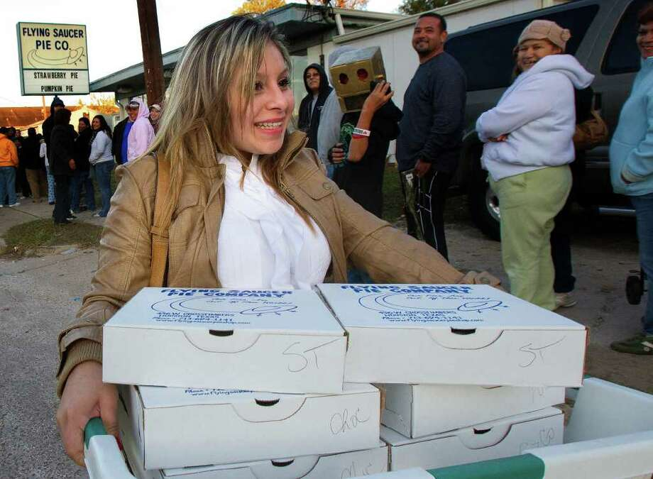 Angela Segundo carries a basket of 16 pies to her car after purchasing them at Flying Saucer Pie Co., Wednesday, Nov. 23, 2011, in Houston. Customers started to line up Tuesday at 2 p.m., to purchase the pies ranging from $10.75-$12.75. Photo: Cody Duty, Houston Chronicle / © 2011 Houston Chronicle