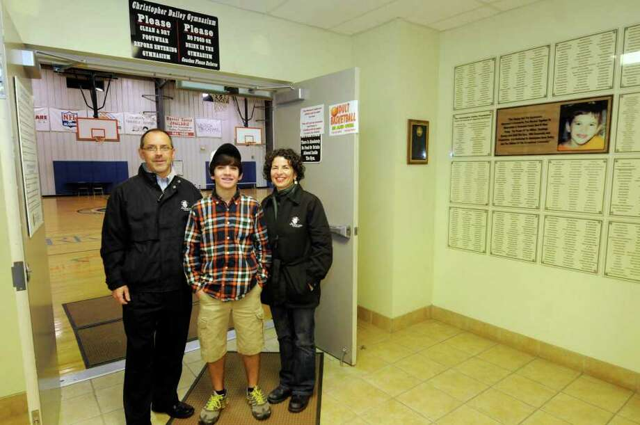 The Dailey family, Mark, Maria & their son, Brendan at the Christopher Dailey gym in Wilton, NY Tuesday, Nov.22, 2011.The family will host the 10th annual Christopher Dailey Memorial Turkey Trot on Thursday. Chris died in 2001 when he was 8. His parents began a foundation in his memory the following year to raise money to build a gym at Gavin Park.( Michael P. Farrell/Times Union) Photo: Michael P. Farrell