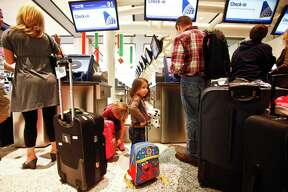 Erin Pilicer, 3, carries her luggage as her father Nihat checks-in their baggage before traveling to Virginia for the Thanksgiving holiday at Terminal C of Bush Intercontinental Airport Houston, Wednesday, Nov. 23, 2011.