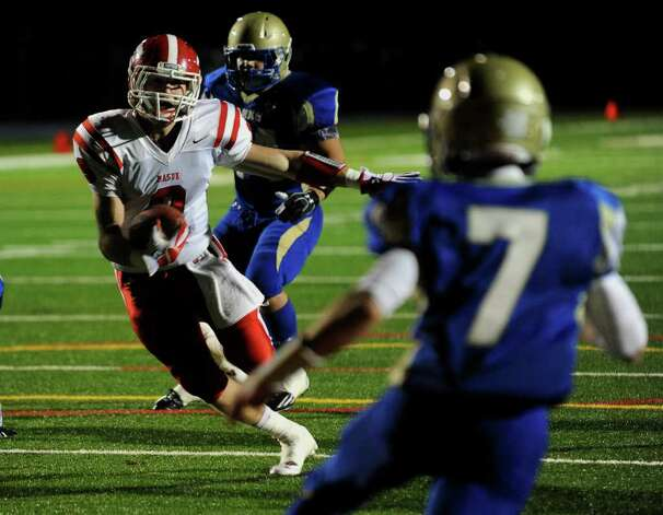 Masuk's #9 Brandon Cusmano carries the ball towards the endzone as Newtown's Dan Herbert waits to intercept, during boys football action in Newtown, Conn. on Wednesday November 23, 2011. Cusmano drove the ball in for a touchdown. Photo: Christian Abraham / Connecticut Post