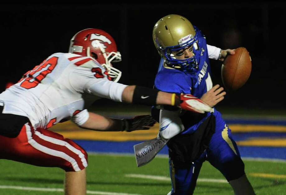Masuk's #30 Pat Tripodi, left, attempts to sack Newtown QB Andrew Tarantino, during boys football action in Newtown, Conn. on Wednesday November 23, 2011. On this play, Tarantino evaded Tripodi but was sacked by Masuk's #95 Bryan Monaco. Photo: Christian Abraham / Connecticut Post